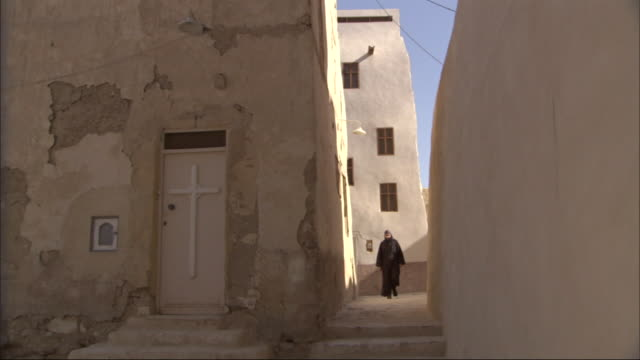 multiple, pan-right - a muslim in traditional dress walks through a quiet alleyway in egypt - cristianesimo video stock e b–roll