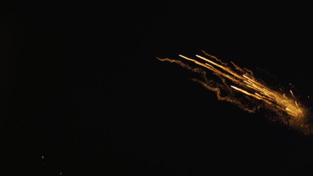 vídeos y material grabado en eventos de stock de multiple rockets fly into frame from right and sparks fly toward camera; smoky explosions blossom - sparks