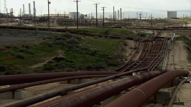 ha multiple rusted oil pipelines running along the ground with storage tanks and power lines in the distance / bakersfield, california, united states - rusty stock videos & royalty-free footage