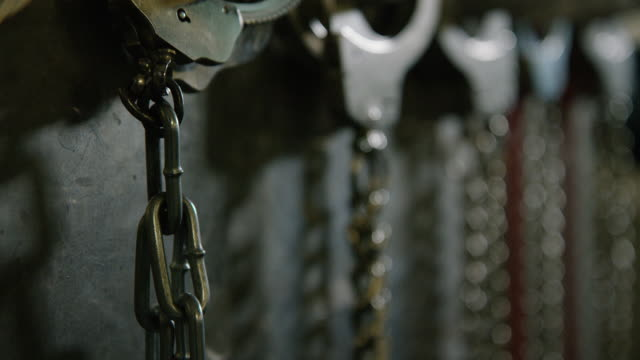 multiple sets of handcuffs hang on a metal wall - prisoner stock videos & royalty-free footage