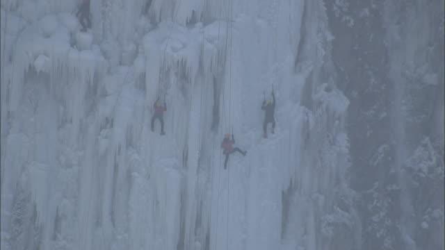 multiple shots of people climbing frozen waterfall - kopfbedeckung stock-videos und b-roll-filmmaterial