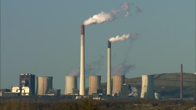 ws multiple smokestacks and reactor towers emitting hot smoke into atmosphere at industrial site in bottrop / bottrop, north rhine-westphalia, germany - 工場の煙突点の映像素材/bロール