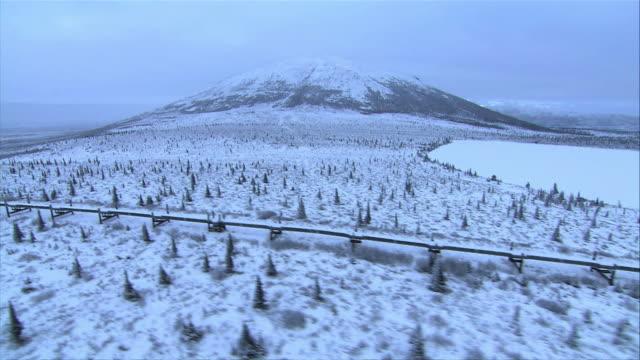 multiple tracking-left - the alaska pipeline stretches across alaska's vast, snowy landscape. / alaska, usa - pipeline stock videos & royalty-free footage