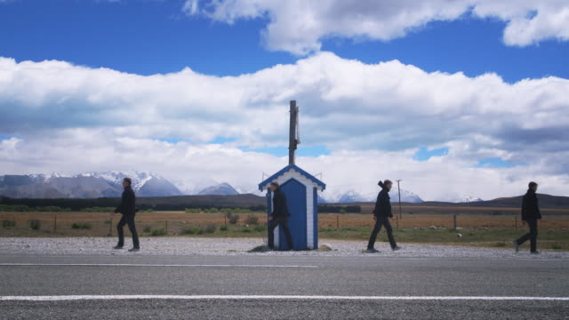t/l, ws, multiplicated man exiting small hut in desert landscape near lake tekapo, south island, new zealand - 同等点の映像素材/bロール