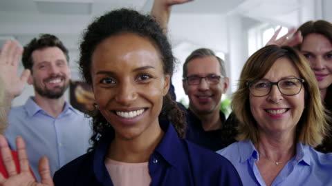 stockvideo's en b-roll-footage met multiraciale business professionals zwaaiende handen in kantoor - waving