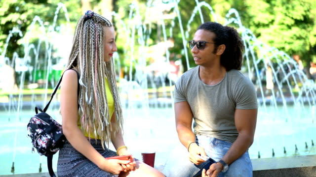 Multiracial couple talking at the fountains