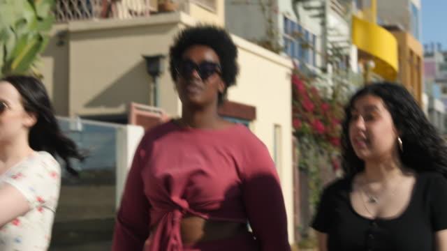 multiracial weibliche freunde zu fuß auf der stadtstraße - biegung stock-videos und b-roll-filmmaterial