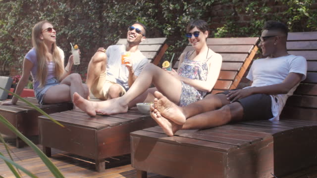 multi-racial friends drinking cocktails by the pool - deck chair stock videos & royalty-free footage