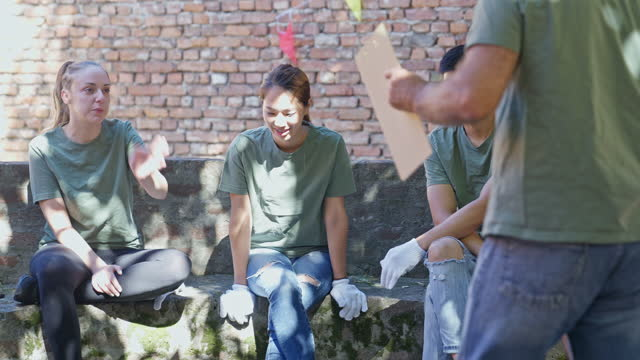 multiracial group of volunteers having a meeting before cleaning environment together - gardening glove stock videos & royalty-free footage