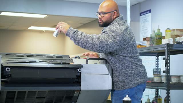 stockvideo's en b-roll-footage met multiracial man in printing factory inspecting press - driekwartlengte
