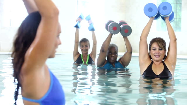 Multiracial older women in water aerobics exercise class