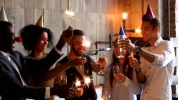 Multiracial young people holding sparklers clinking glasses celebrating party, cheers