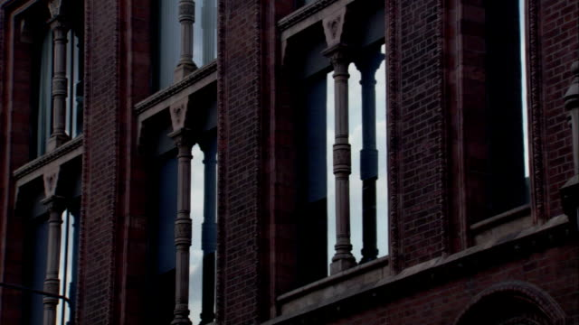 a multi-story brick building has elaborate stonework on its facade and window trim. available in hd. - leeds stock videos and b-roll footage