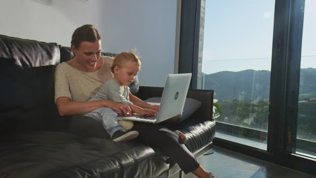 vídeos y material grabado en eventos de stock de empresaria de la multitarea con su hijo en casa - adulto de mediana edad