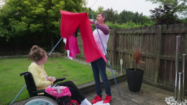 multitasking dad with happy disabled daughter - scoliosis stock videos and b-roll footage