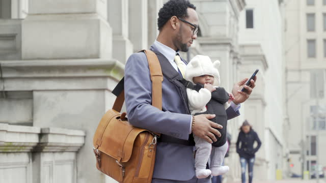 multi-tasking modern father using mobile device - baby carrier stock videos & royalty-free footage