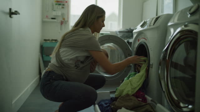 multitasking mother carrying baby and loading clothing into washing machine / lehi, utah, united states - lavori di casa video stock e b–roll