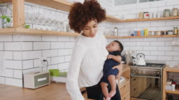 Multi-Tasking Mother Holds Sleeping Baby Son Whilst Cleaning And Working On Laptop In Kitchen