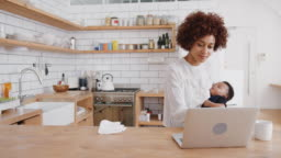 Multi-Tasking Mother Holds Sleeping Baby Son Whilst Working On Laptop In Kitchen
