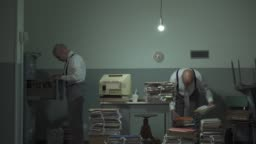 Multitasking office worker searching for files in his office