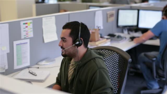 vidéos et rushes de multitasking worker in office cubicle talks on headset, enters info in computer (dolly shot) - casque téléphonique