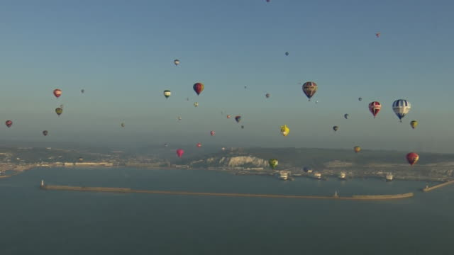 a multitude of hot air balloons flying across the english channel in an attempt to break the world record - イギリス海峡点の映像素材/bロール