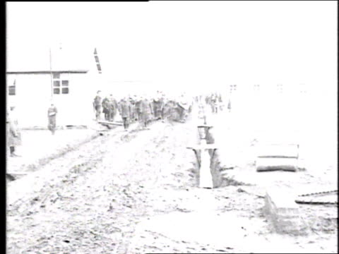 vídeos de stock e filmes b-roll de multitudes of troops in full field kit marching in formation on wet, muddy road beside barrack / france - super exposto