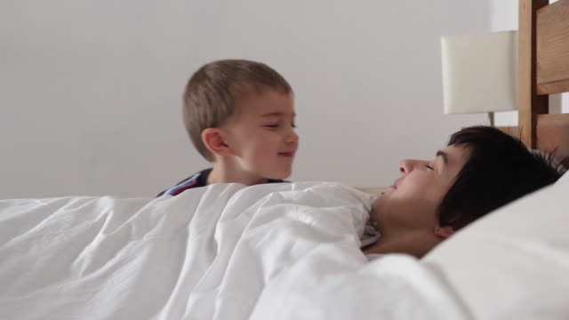 mum asleep, boy pops his head up beside bed and kisses mum/uk - lying on back stock videos & royalty-free footage