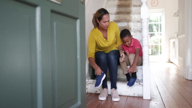 Mum helping son with his shoes