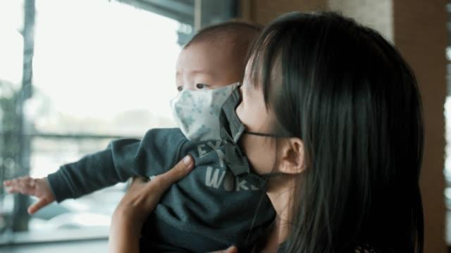 ママは彼女の息子を保持し、大気汚染マスクを着用 - 安全衛生保護具 マスク点の映像素材/bロール