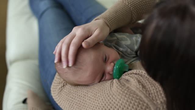 mum lying on sofa, cradling newborn baby. - pacifier stock videos and b-roll footage