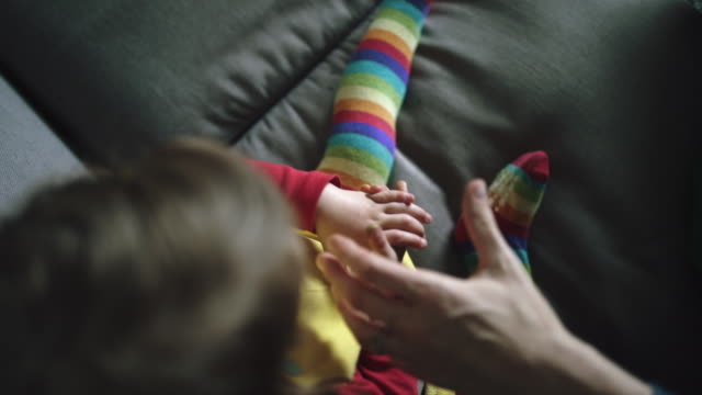mum painting rainbow on little girls hand - annual event stock videos & royalty-free footage