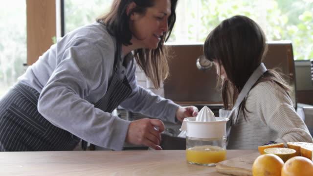 vídeos y material grabado en eventos de stock de ws mum tying girl's apron in kitchen - delantal