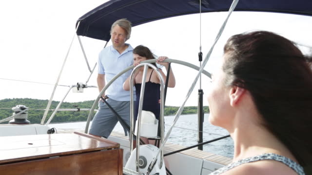 mum watching her young daughter helping to steer yacht. - tutina video stock e b–roll