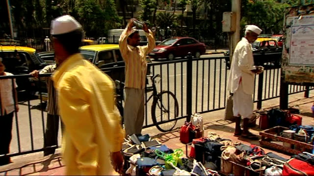 vídeos de stock, filmes e b-roll de general views of traffic and tiffinwallahs more shots of dabbawalas along on station platform dabbawala along up street carrying large crate filled... - packed lunch