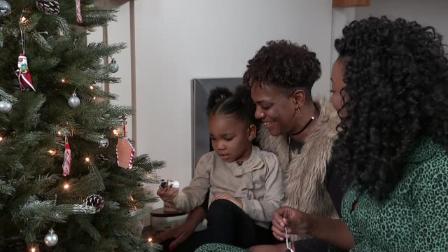 mums launch inclusive christmas tree decorations with black santa and angels; england: london: int natalie duvall and alison burton looking at black... - christmas tree stock videos & royalty-free footage