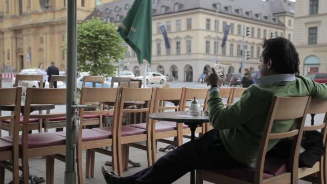 munich beer garden, medium shot, man drinking alone by the road. - abgeschiedenheit stock-videos und b-roll-filmmaterial