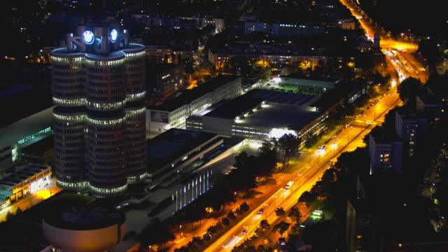 munich bmw cylinder and bmw museum at night - antenne stock-videos und b-roll-filmmaterial