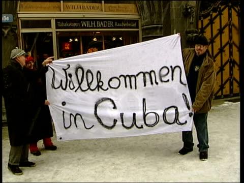vídeos de stock, filmes e b-roll de munich ms protestors holding banner 'willkommen in cuba' cbv banner around shoulders of demonstrator with word 'why' - alta baviera