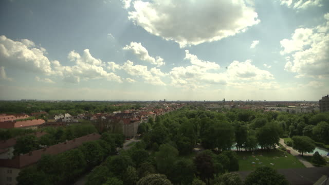 Munich from above, roofs of houses, trees, sunny, blue sky, clouds, park