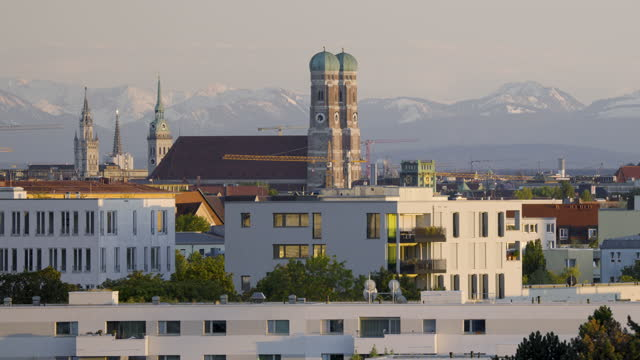 munich landmark frauenkirche with alps in the background - wop productions stock-videos und b-roll-filmmaterial