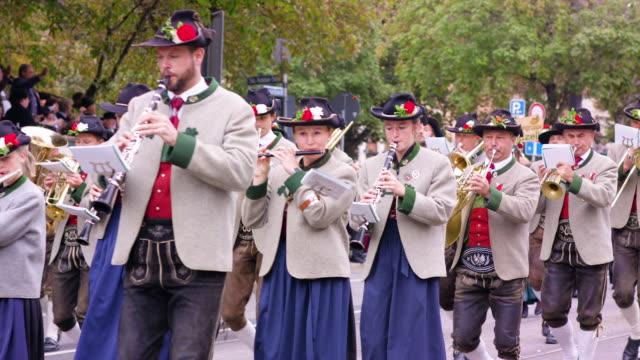 munich oktoberfest traditional costume parade brass band playing and walking - ブラスバンド点の映像素材/bロール