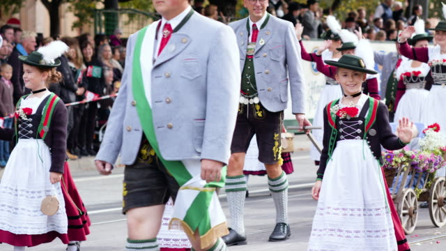 munich oktoberfest traditional costume parade girl with traditional hat waving at camera - tradition stock-videos und b-roll-filmmaterial