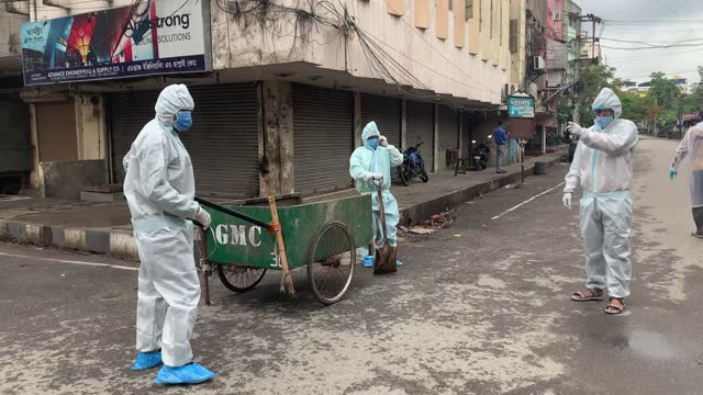vídeos de stock, filmes e b-roll de municipal workers wearing protective wear collecting garbage on a cart at fancy bazar area, 15 persons found covid19 coronavirus positive in this... - câmara parada