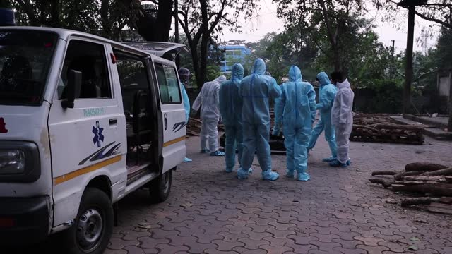 municipality workers with family members wearing ppe kit perform last rites for someone who died of the covid-19 coronavirus disease, at a... - men stock videos & royalty-free footage