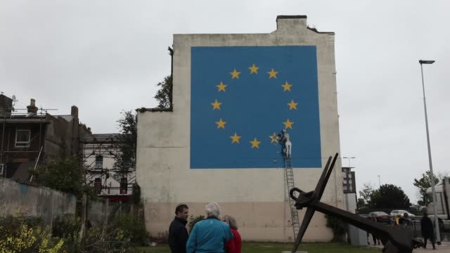 mural depicting a european union flag being chiseled by a workman sits on the side of a disused building near the ferry terminal in dover, u.k., on... - 2016 video stock e b–roll