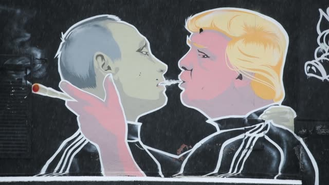 a mural depicts us president donald trump blowing marijuana smoke into the mouth of russian president vladimir putin on the wall of a barbque... - männerfreundschaft stock-videos und b-roll-filmmaterial