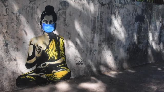 vídeos de stock e filmes b-roll de mural of buddha sitting cross-legged and wearing a face mask appears in mumbai, as do hoardings promoting hand-washing and other precautionary... - cross legged