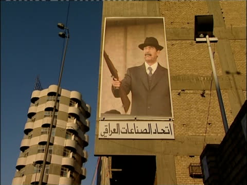 A mural of Saddam Hussein holding a gun hangs on a building in Baghdad.