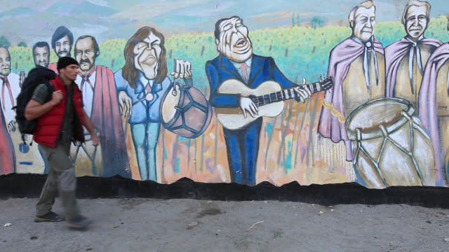 mural on wall, travelling mna walks past - female likeness stock videos & royalty-free footage